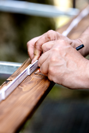 Close-up of hands, wooden plank is measured with the help of a yardstick and made a mark with a pencil