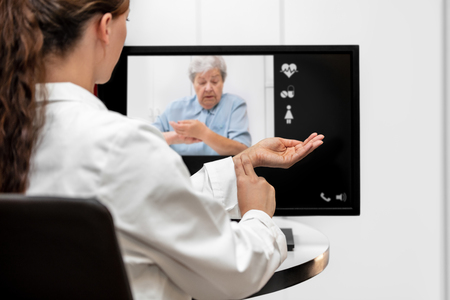 Doctor and senior woman taking the pulse together, telemedicine and videotelephony for medical health care Banque d'images