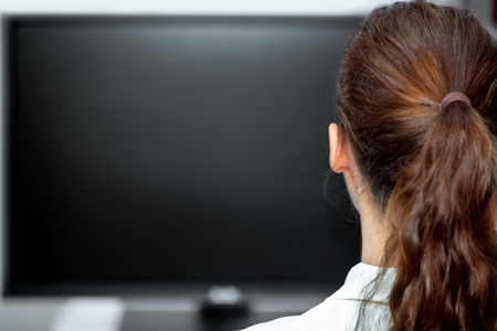 Young woman sitting in front of a black monitor or tv, backview and copyspace Stock Photo