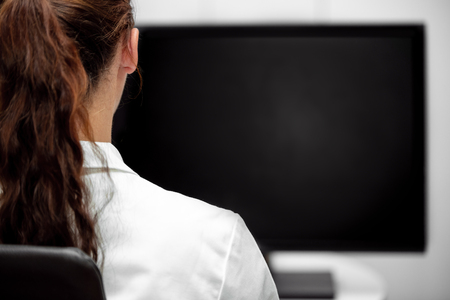 Backview, young lab assistent or female doctor looking at a black desk or monitor, copyspace