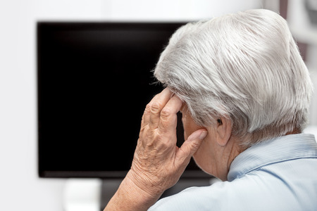Elderly woman with headache sitting in front of a desk or tv, concept mental overload and stress, copyspace Stok Fotoğraf