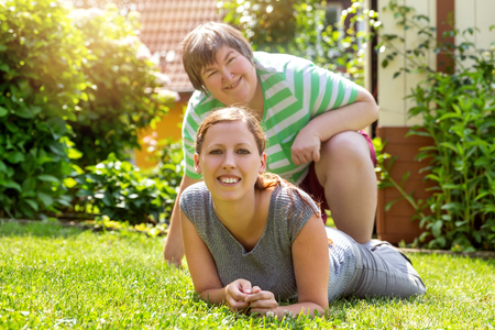 lachende geestelijk gehandicapte vrouw en een vriend in de tuin, zonnig weer