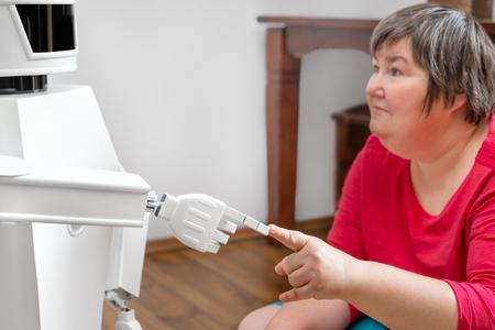 Der autonome Roboter des medizinischen Dienstes berührt mit seinem Finger den Finger einer geistig behinderten Frau