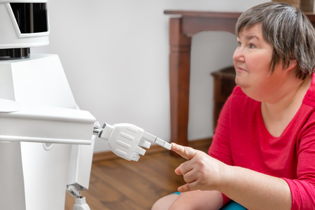 autonomous medical service robot is touching with his finger the finger of an mentally disabled woman