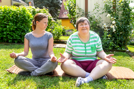 two women, one of them a fitness or yoga coach, are doing some yoga or relaxation exercises, on woman is mentally disabled