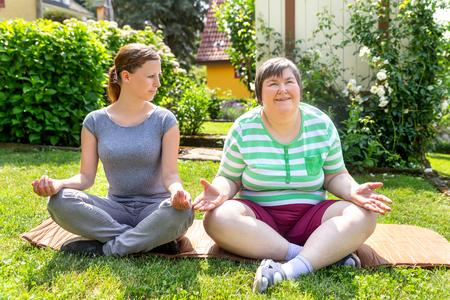 Zwei Frauen, eine davon eine Fitness- oder Yoga-Trainerin, machen Yoga- oder Entspannungsübungen, wobei die Frau geistig behindert ist Standard-Bild