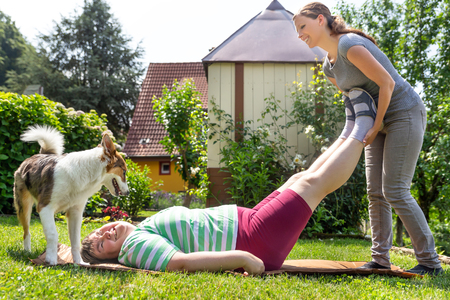 mentally disabled woman is getting trained by a young caregiver or professional, laying on a lawn, doing some exercises