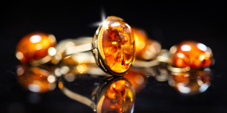 panorama of jewelry with amber stones, amber necklace ring and earring and pendant with noble metal like gold, in front of a black background on a black stone with reflection