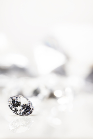 still with expensive cut diamonds in front of a white background, reflections on the ground. Lot of copyspace