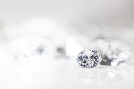 toujours avec des diamants taillés chers devant un fond blanc, reflets sur le sol. Beaucoup de copyspace