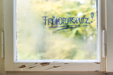 window with water and dust on it, german word frühjahrsputz which means spring cleaning
