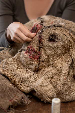 woman is sewing a scarecrow mask and costume for carneval or halloween, maybe a prop for a movie or theatre Stock Photo