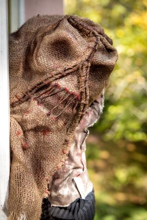 Hombre con la máscara de un espantapájaros espeluznante mirando a través de una ventana