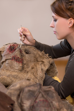 woman is sewing a scarecrow mask and costume for carneval or halloween, maybe a prop for a movie or theatre Stockfoto