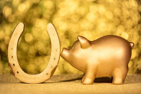 Hufeisen und Schwein in Gold, Symbole des Glücks
