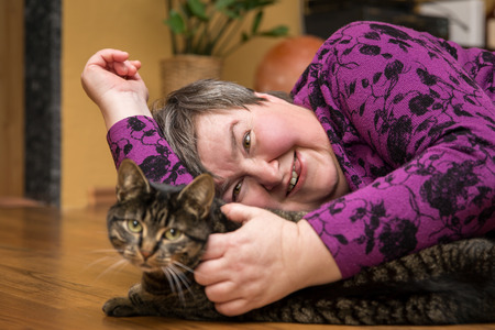 Disable woman cuddling a cat, animal-assisted therapy