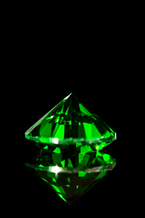 Green emerald in front of black background, flawless gem, closeup