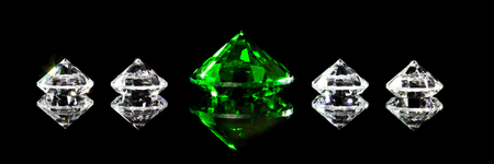 Panorama, diamonds and a green emerald in front of black background, closeup