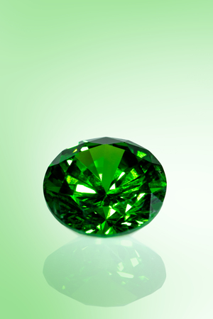 Green shiny emerald in front of green background, brilliant cut, closeup Stock Photo
