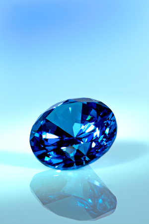 Blue diamond or sapphire in front of blue background, brilliant cut, closeup