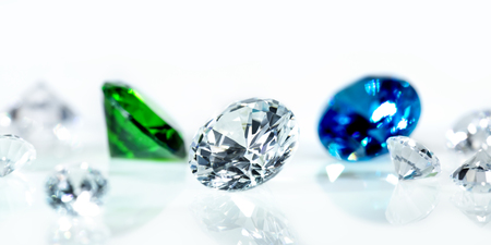 Flawless diamonds, blue sapphire and a green emerald in front of white background, banner Stock Photo