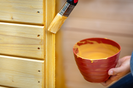 Woman glazes or paints wooden boards with pines colored glaze or varnish Stock Photo