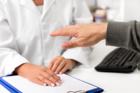 man showing his tremulous hand on the clinic, concept tremor, parkinson and stress, bodypart