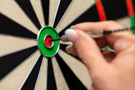 Closeup, woman playing steeldart, professional dart sport trainee, bullseye