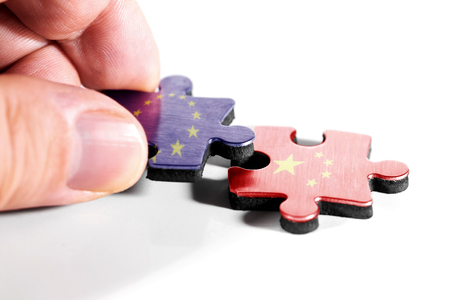 Two puzzle pieces with the flags of Europe and the People's Republic of China, isolated against white background
