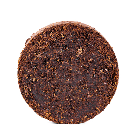 Round pressed coffee grounds isolated against white background
