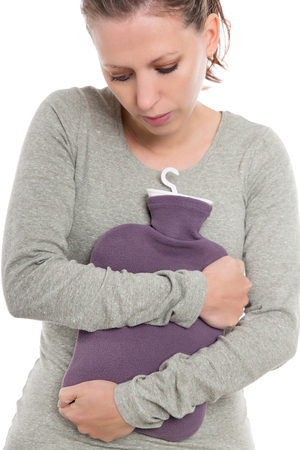 jeune femme souffrant de maux d'estomac, de douleurs à l'estomac ou de douleurs abdominales, bombasse et sac d'eau chaude, isolée