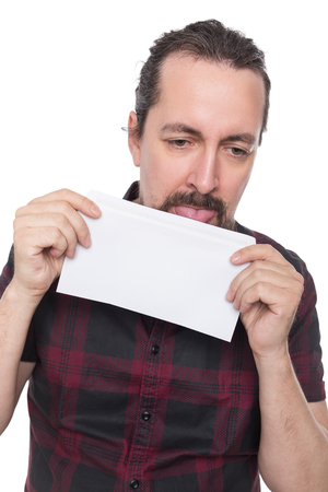 caucasian man holding and licking a white envelope, isolated on white