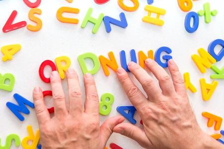 muchas letras coloridas sobre una mesa, manos formando la palabra alemana ordnung, que significa mantener el orden