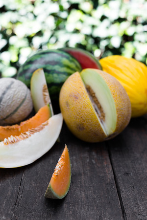 topview on a lot of various fresh and sliced melons on a dark wooden background