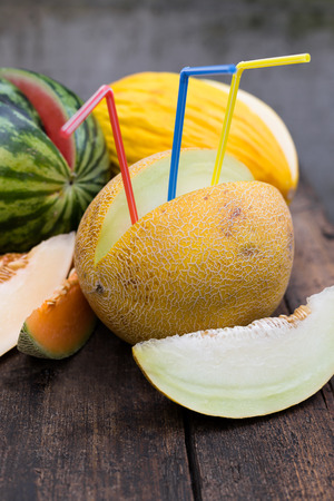 various melons with colorful drinking straws in it