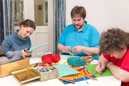 Two caretakers with a mentally disabled woman making a Ergotherapy Stockfoto