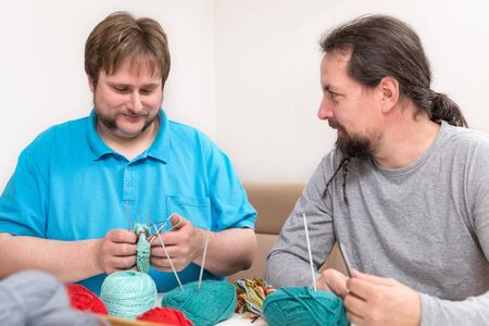 two men are crochet together at home