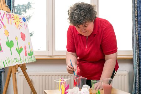 a painting Therapy with a mentally disabled woman 스톡 콘텐츠