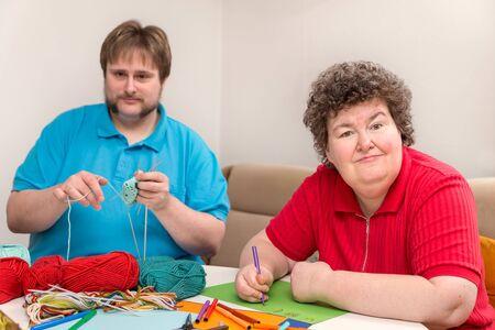 een man en een verstandelijk gehandicapte vrouw zijn aan het knutselen Stockfoto