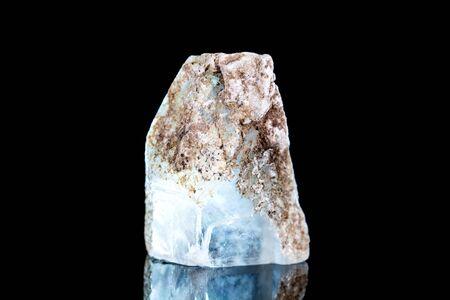 Piedra mineral selenita cruda delante de fondo negro, mineralogía y esoterismo