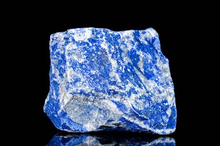 Raw blue lapis lazuli mineral stone in front of black background, mineralogy and esotericism