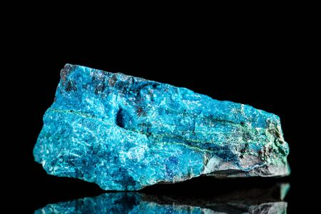 Raw blue apatite mineral stone in front of black background, mineralogy and esotericism
