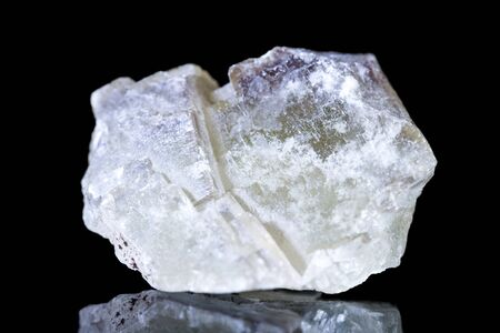 Raw fluorite mineral stone in front of black background, mineralogy and esotericism