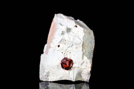 Raw garnet mineral stone on mother rock in front of black background, mineralogy and esotericism