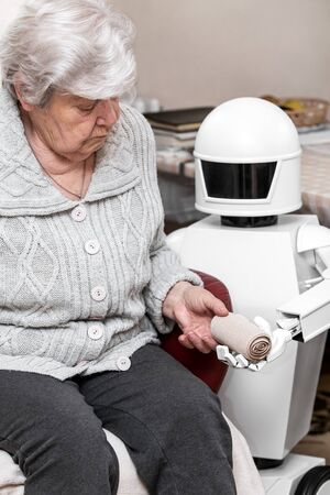 autonomous caregiver robot is holding a elastic bandage, giving it to an senior adult woman in her living room, concept ambient assisted living