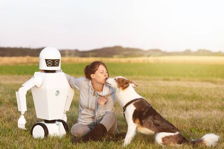 pretty woman with her dog and her robot are sitting on a field in the nature