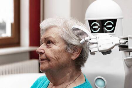 ein Pflegeroboter kämmt die Haare einer weiblichen Seniorin, Konzepte wie Haushalts-Pflegeroboter oder helfende Technik in der Medizin