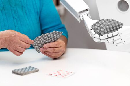 ambient assisted living service robot is playing a card game with a senior adult woman, concepts like robotic caregiver in the household or old folks home