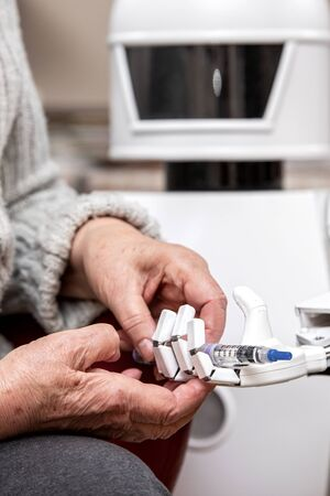 autonomous caregiver robot is holding a insulin syringe, giving it to an senior adult woman in her living room, concept ambient assisted living Stock Photo - 130686683