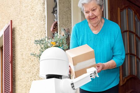 autonomous ai artificial intelligence robot is delivering parcels or boxes, senior woman is receiving post from an futuristic robotic delivery service 版權商用圖片